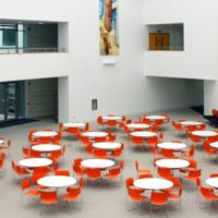 Large light filled atrium splashed with colourful chairs