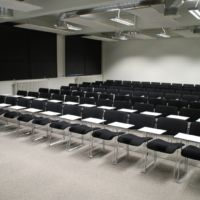 World-class stacking linking chairs with individual retractable removeable writing work surface